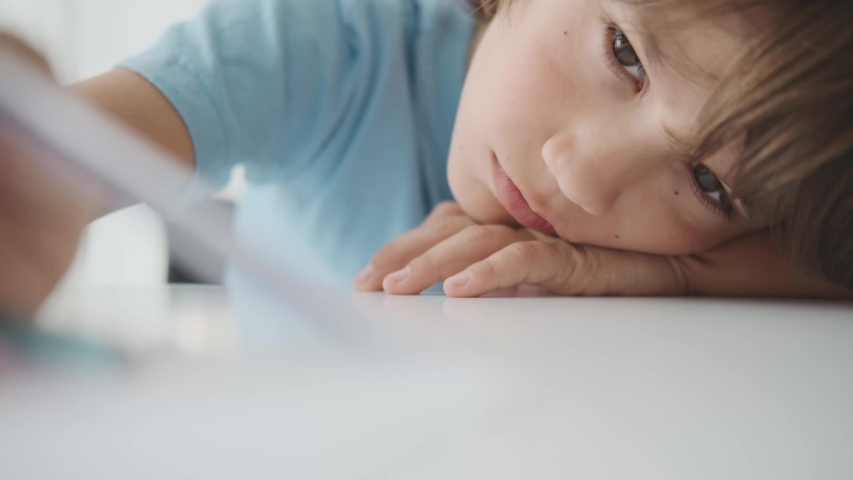 A bored schoolboy boy lies on a desk and looks at a pen. A sad boy 10-12 years old sits at a desk with a notebook, lazily scratches a pen. Portrait of a pupil