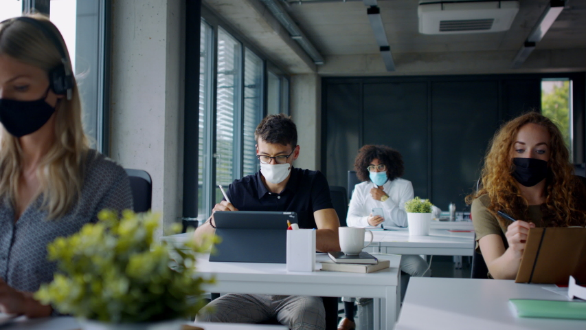 Young people with face masks back at work or school in office after lockdown. Royalty-Free Stock Footage #1056564503