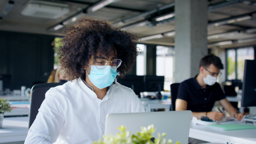 Young people with face masks back at work or school in office after lockdown. Royalty-Free Stock Footage #1056564515