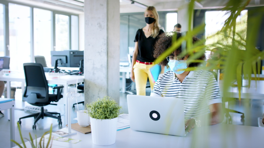 Young people with face masks back at work in office after lockdown, greeting. Royalty-Free Stock Footage #1056564557