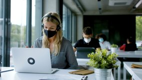 Young woman with face mask back at work in office after lockdown, having video call.
