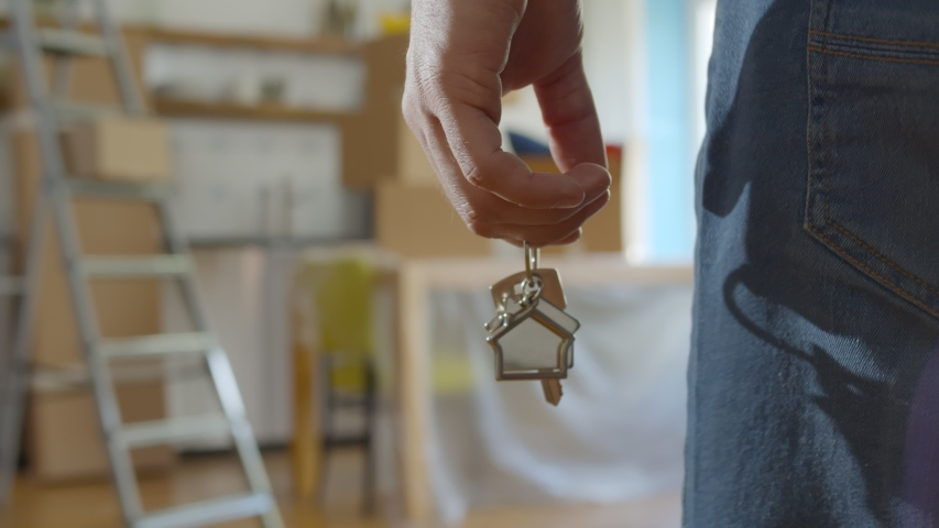 Close up of man holding key with house keychain in hand and walking in new apartment with cardboard boxes and ladder on background. Guy moving in new home. Buying or renting real estate concept