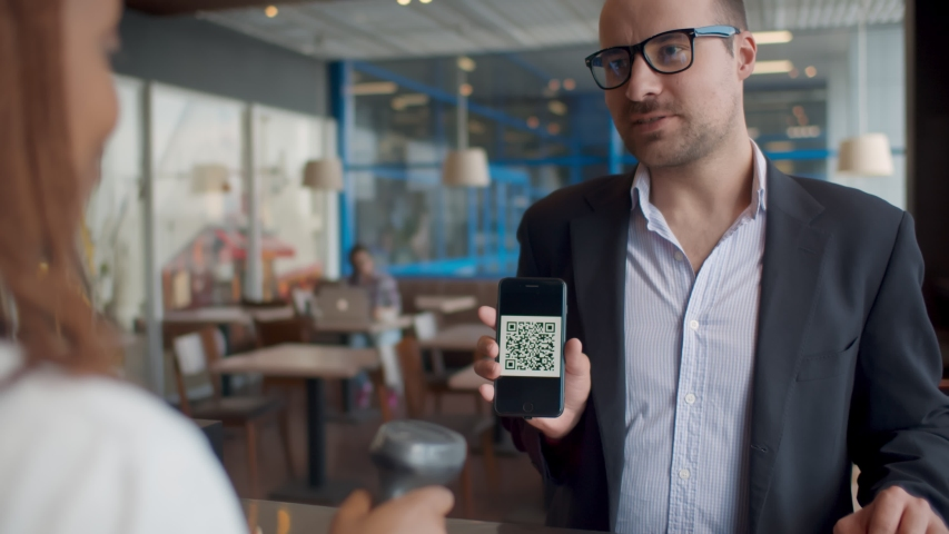 Businessman pay by scanning QR code on smartphone in coffee shop. Man customer using qr-code on smartphone for payment to owner at cafe. Small business and cashless technology concept Royalty-Free Stock Footage #1056569012
