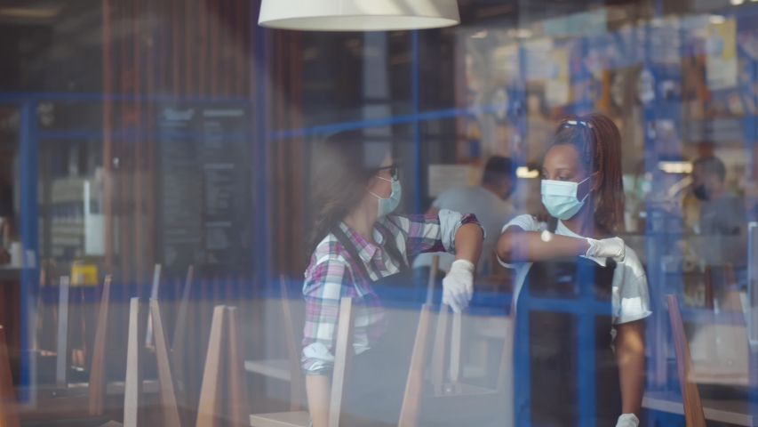 View through window of multiethnic waitresses in protective masks and gloves doing elbow bumps greeting in restaurant before opening. Covid-19 restrictions and small business crisis concept