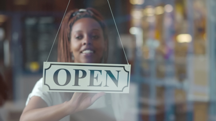 Small business african female owner smiling while turning sign for opening of cafe. Happy afro-american waitress in apron turning sign on door opening restaurant in morning.