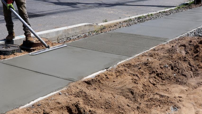 Construction mason building a screed coat cement a laborer floats a new concrete sidewalk