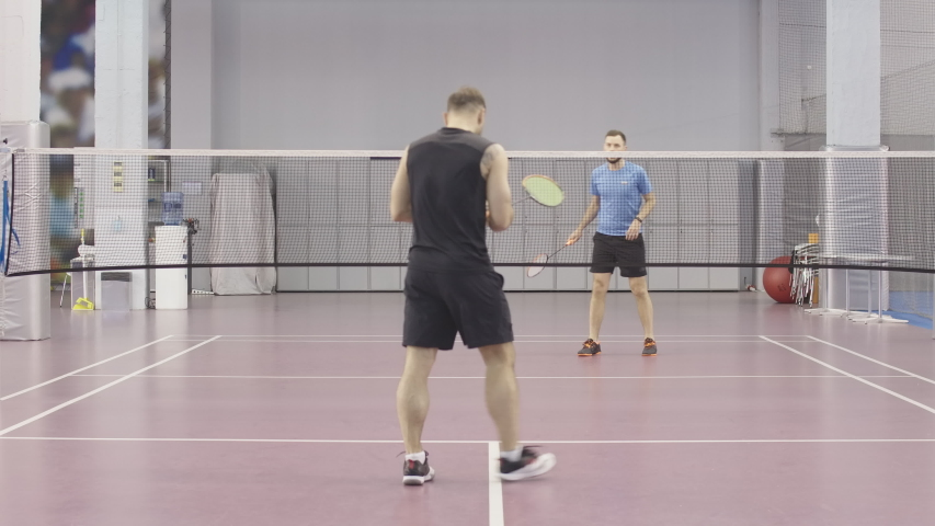 Sportive Caucasian men playing badminton indoors. Wide shot portrait of two young sportsmen exercising in gym. Athletic guys training on indoor court with rackets and shuttlecock.