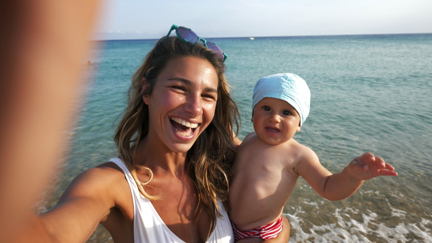 Authentic shot of happy carefree smiling neo mother and her newborn baby making selfie or video call to father or relatives on a beach with seaside in a sunny day.  Royalty-Free Stock Footage #1056581264