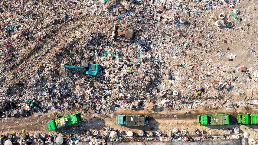 Time lapse of Aerial top view of A Huge Waste, garbage, dump, rubbish landfill. A landfill compactor, group of workers sort out the garbage in the landfill. Trash trucks dump waste polluting products. Royalty-Free Stock Footage #1056592418