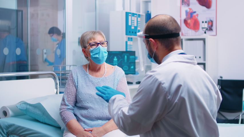 Old retired senior woman wearing a mask at doctor consultation during COVID-19 pandemic. Healthcare system, disease treatment in modern professional private clinic or hospital | Shutterstock HD Video #1056594218
