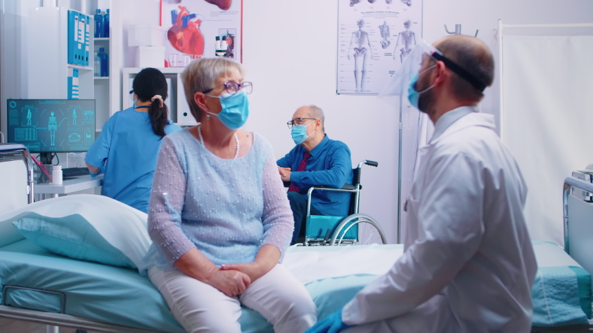 Two old senior persons at doctor wearing masks and talking with nurse and doctor in protective wear. Modern private clinic or hospital ward during COVID 19 pandemic. Healthcare medicine appointment | Shutterstock HD Video #1056594227