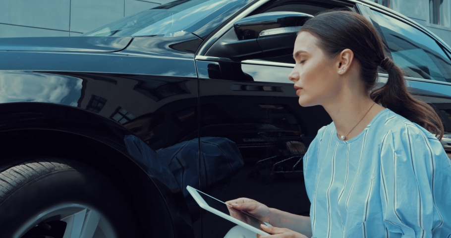 Serious woman touching car and using digital tablet