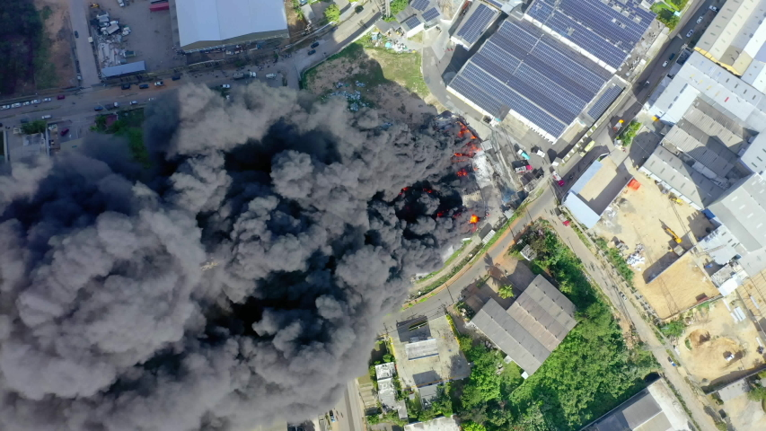 Aerial, top down above firefighters trying to quell the fire, in front of a building on fire, a huge black smoke cloud, in Haina, San Cristobal, Dominican Republic - screwdriver, drone shot   Shutterstock HD Video #1056596498