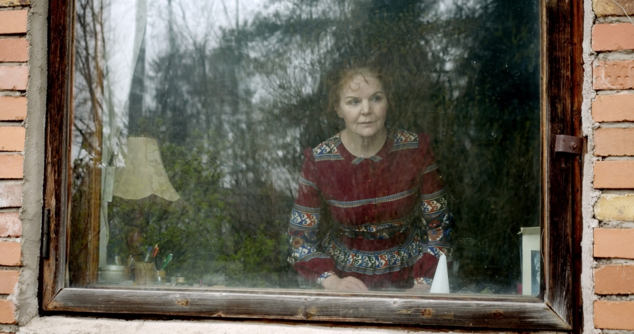 Old middle aged woman looks out the window and waits for someone or something. self-isolation. waiting for children. sad woman in the window.