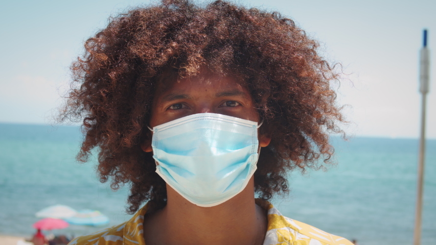 Black latin american man with afro haircut in medical mask during coronavirus lockdown, pandemic, happy young hispanic teenager post covid portrait, student in protection safety mask Royalty-Free Stock Footage #1056605804