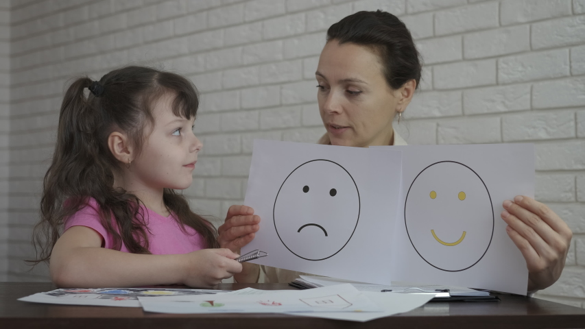 The mood of the child at the psychologist. Female psychologist shows drawings with mood.