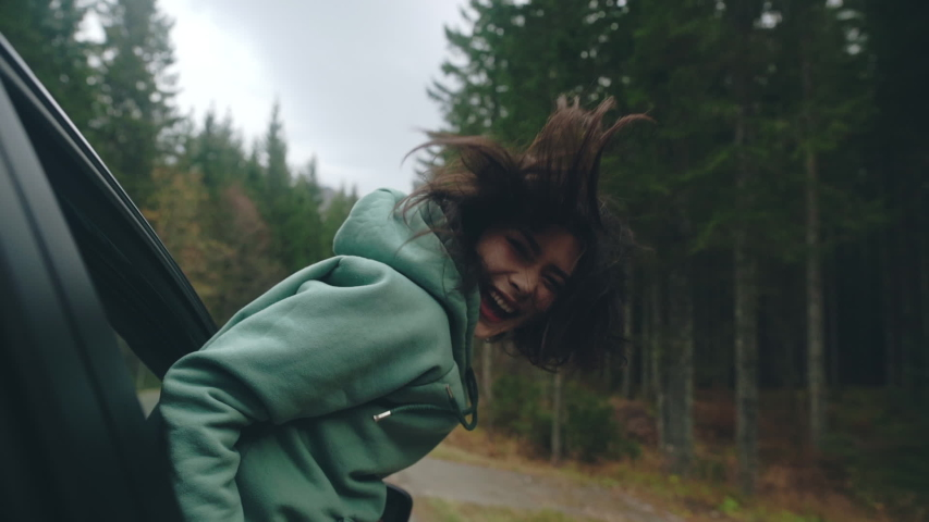Close-up face of young woman traveling by car while road trip. Woman pulling her face and hands out of car window and enjoying speed while her hair flying away because of the wind. Concept of freedom.