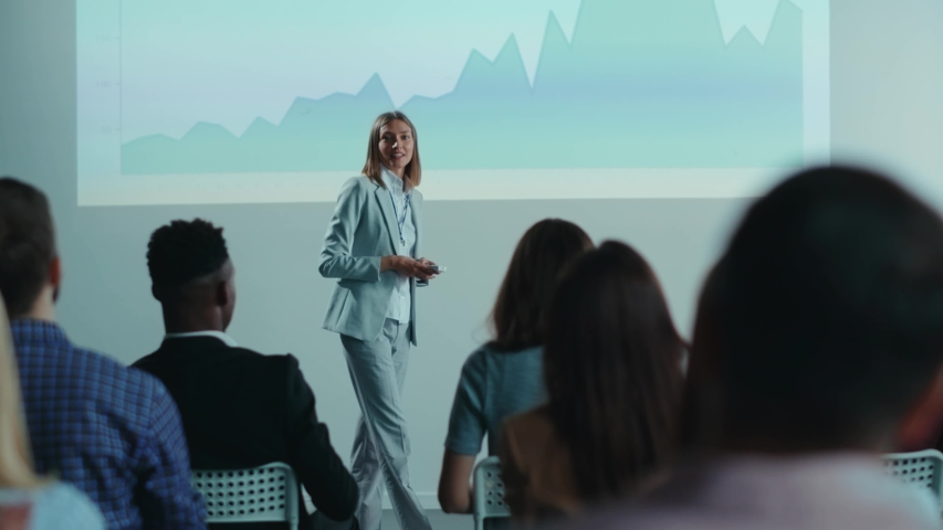 Beautiful female coach businesswoman answers questions from the audience on public conference. Discussion. Presentation screen. Summit. Business seminar.