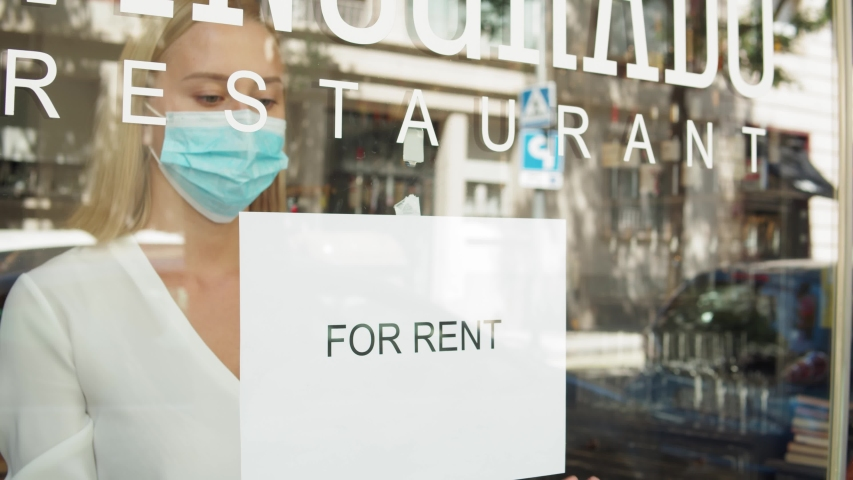 cafe or restaurants and business closed banking financial crisis after coronavirus quarantine is over. woman with face mask turning sign for rent to door shop. small business sale after post covid Royalty-Free Stock Footage #1056615122