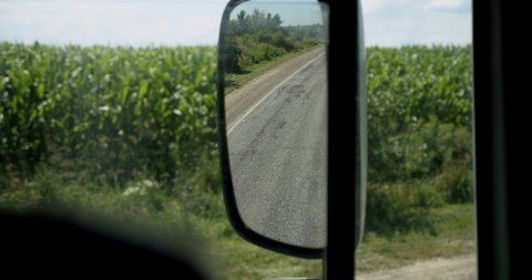 Truck driver View for window and mirror. Man driving car at country road on warm summer day. Slow motion Close up