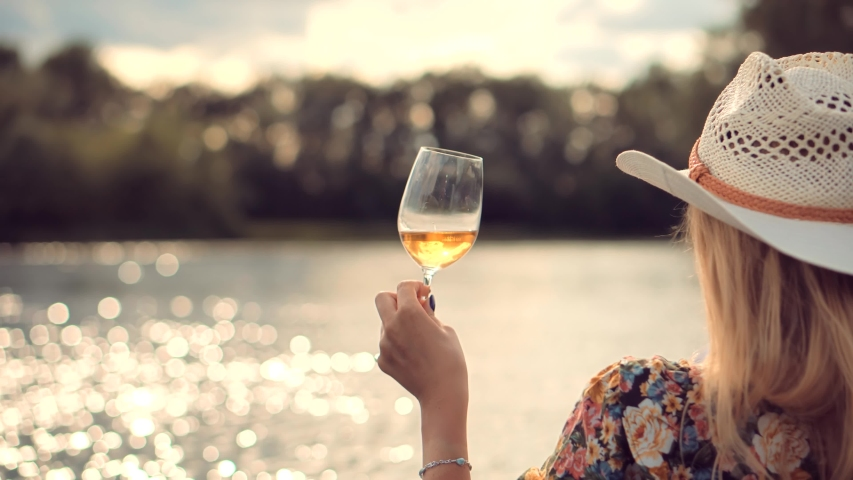 Woman Drinking White Wine Outdoor.Pretty Lady Relaxing After Hard Working Day And Celebrating Holidays Vacation.Romantic Evening Enjoying With Wineglass.Happy Woman Hold Glasses And Drinking Wine. | Shutterstock HD Video #1056624686