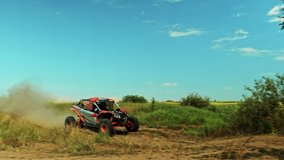 SLOW MOTION: Buggy car is driving fast in a cross country road. Fast rally auto is going with big clouds of dust. Speed riding of a racing off-road car in the rural road. Cinematic clip.