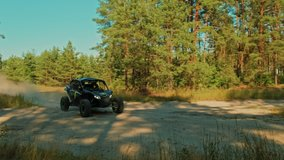 Cinematic clip of a buggy car is driving in cross country road. Buggy is driving with big clouds of dust. Racing off-road car in the forest road with a sound engine.
