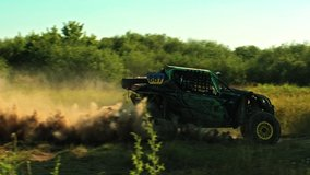 Buggy car going fast in cross country road. Fast rally auto is going with big clouds of dust. Speed riding of a racing off-road car in the rural road. Cinematic clip.