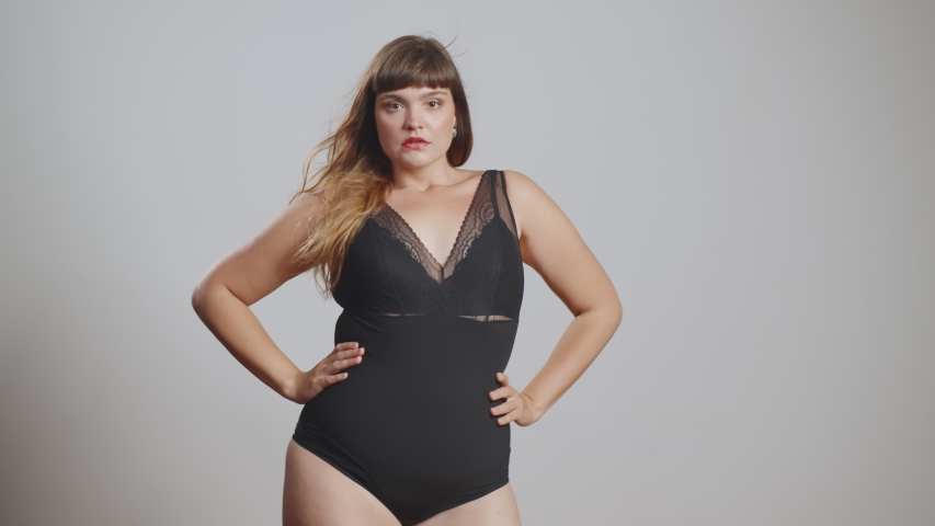 Sensual overweight woman in bodysuit posing at camera in studio. Portrait of attractive young plus size woman with hands on waist isolated over grey background