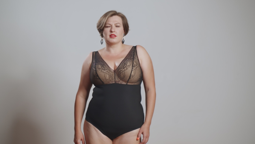 Young beautiful plus size model with stylish haircut and makeup in underwear. Xxl woman on gray studio background posing at camera. Body positive concept