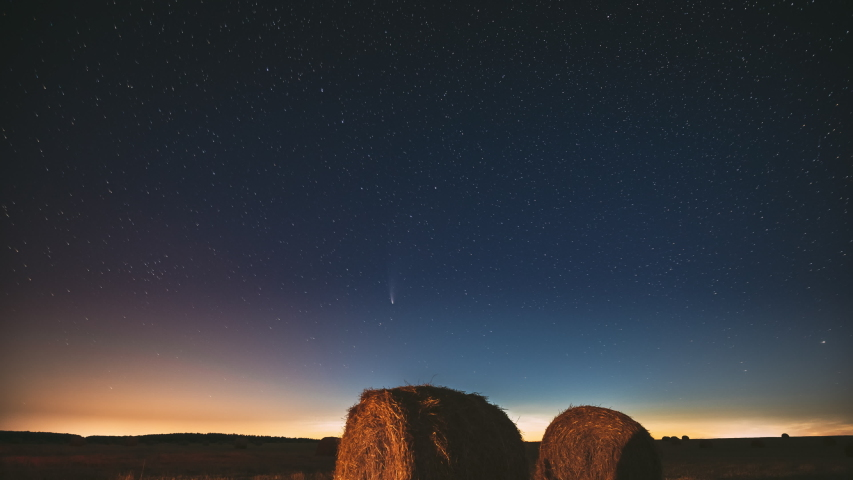 Comet Neowise C/2020 F3 In Night Starry Sky Above Haystacks In Summer Agricultural Field. Night Stars Above Rural Landscape With Hay Bales After Harvest. Agricultural Concept. 4K Timelapse   Shutterstock HD Video #1056640265