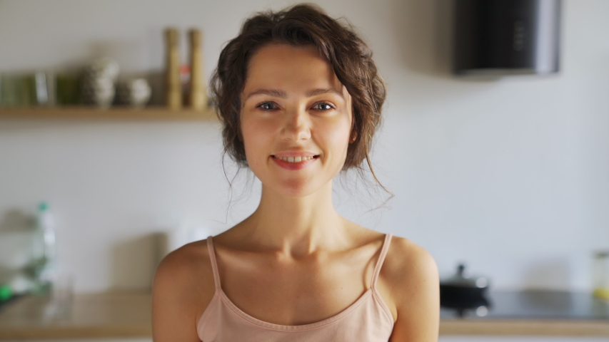 Young smiling beautiful woman pretty face looking at camera posing alone at home standing in kitchen. Girl with clean, healthy, glowing skin. Happy millennial caucasian girl close up front portrait    Shutterstock HD Video #1056640646