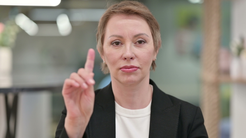 Serious Businesswoman saying No by Finger Sign