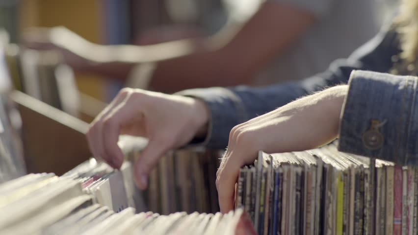 Couple Stand Next To Each Other At Record Store Sidewalk Sale, Young Woman Pulls Out A Few That She Might Like, Then Continues Looking (4K)