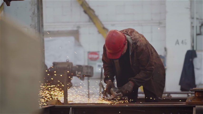 Factory Worker Grinds Metal Construction using angle grinder. Bright Golden Sparks comes out, Heavy Manual Work at Modern Steel Making Industry. Slow Motion.  | Shutterstock HD Video #1056645845