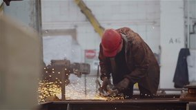 Factory Worker Grinds Metal Construction using angle grinder. Bright Golden Sparks comes out, Heavy Manual Work at Modern Steel Making Industry. Slow Motion.
