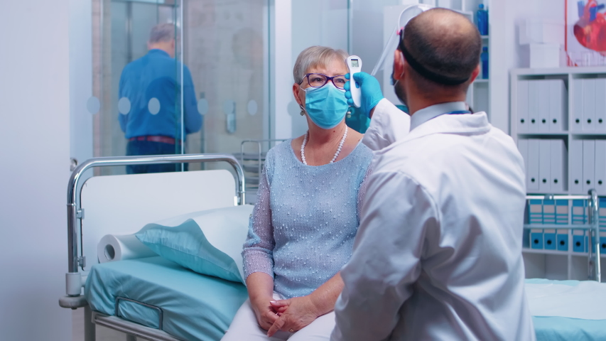 Helthcare worker checking the old woman temperature with a thermometer gun. Retired senior pensioner wearing a mask and healthcare worker in protective equipment for consultation. COVID 19 | Shutterstock HD Video #1056649877