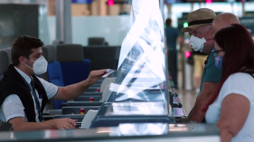 Checking counter documents registration flights at airport. An airline representative wearing mask on face makes passenger registration. Travel during quarantine of the coronavirus infection COVID-19.