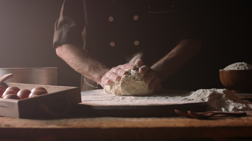 Senior professional chef kneading floured dough at bakery, mature retiree enjoying hobby making homemade bread using traditional recipe isolated on black background close up 4k footage Royalty-Free Stock Footage #1056653159