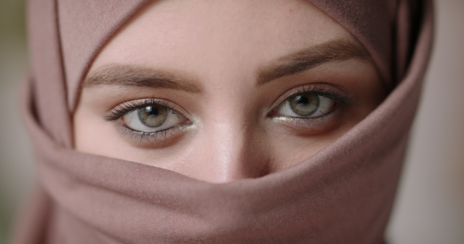 Face with natural make up of attractive muslim gir wearing traditional hijab scarf. Her brown and green eyes looking at camera - beauty, islam concept extreme close up 4k footage | Shutterstock HD Video #1056653285