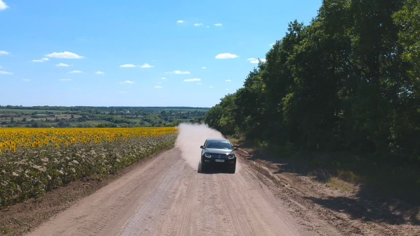 Aerial shot of black pickup truck fast riding through empty rural road. Off road vehicle going on dusty route near field. Flying over car driving at countryside way on summer day. Concept of farming | Shutterstock HD Video #1056653396