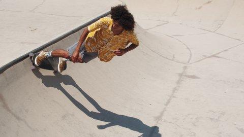 Professional skater in bowl skatepark doing tricks, skateboarder carving a turn in a deep concrete bowl, latin hispanic man on extreme surfboard, summer sports