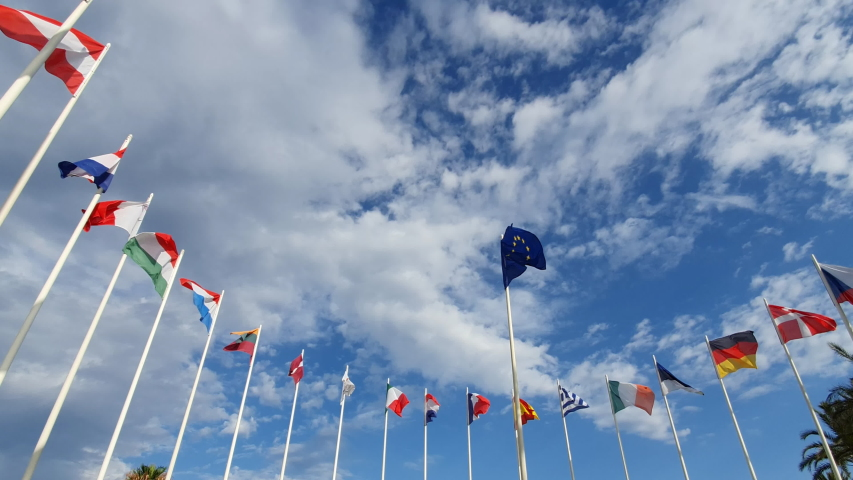 Flag of European Union and EU member flags on the background against a cloudy sky Royalty-Free Stock Footage #1056662438