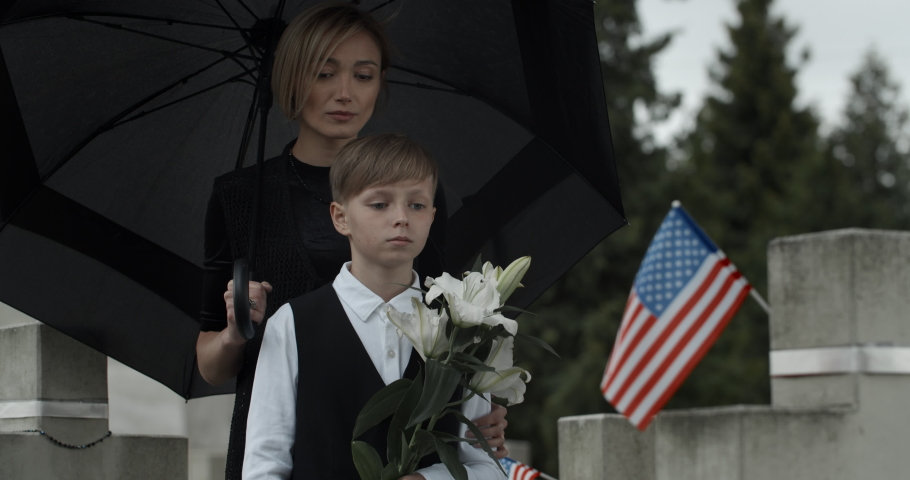 Mom and child standing near gravestone with american flag under umbrella. Widow and young boy with white lily flowers honoring husband and father at cemetery. Concept of memorial day.