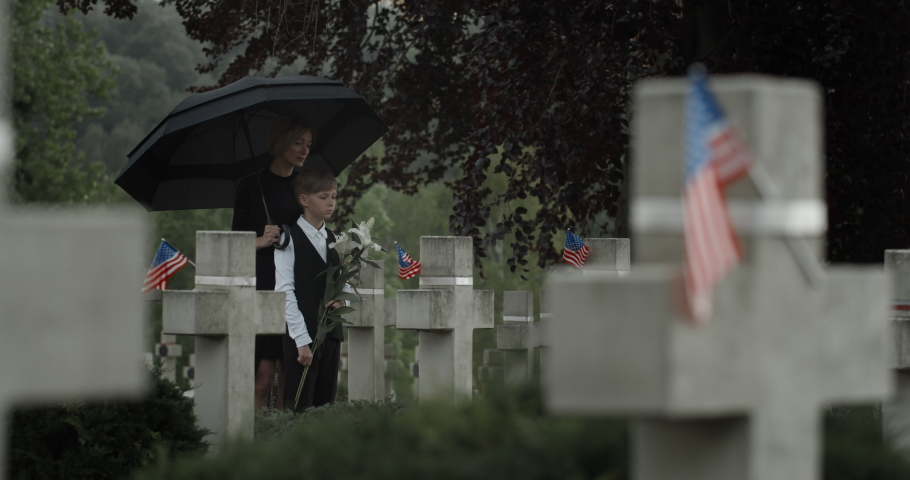 Teen kid son Widow and her standing under umbrella at cemetery. Mother and young boy near gravestone. Concept of memorial day. American flags on stone crosses.