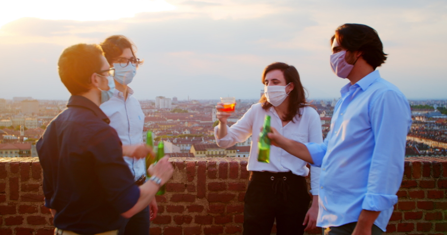 Masked people drink at the bar. A Group of friends celebrate quarantine ending. New rules in bars and restaurants. Tourists in Italy on vacation. European Generation Z at a coronavirus party. Royalty-Free Stock Footage #1056664430
