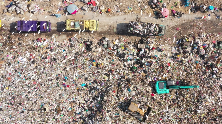 Aerial top view of A Huge Waste, garbage, dump, rubbish landfill. A landfill compactor, group of workers sort out the garbage in the landfill. Trash trucks dump waste polluting products. | Shutterstock HD Video #1056664433