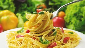 Plate of cooked italian pasta, spaghetti on fork with tomatoes and basil leaves, 4K UHD video footage