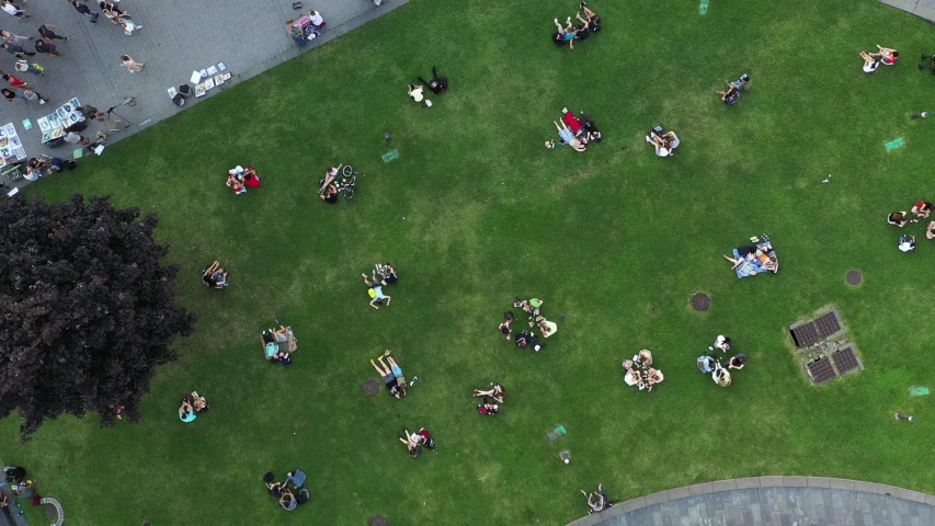 Ending social distancing and quarantine - Couples in love and other people rest on the green lawn at the end of the day - the end of the quarantine. Ending social distancing in Kyiv. Aerial View.