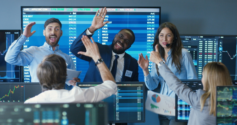 Mixed-races happy cheerful males and females brokers smiling and giving fives to each other after suceess in trading. Exchange office with monitors and rates. Multietnic traders celebrating. Royalty-Free Stock Footage #1056665351